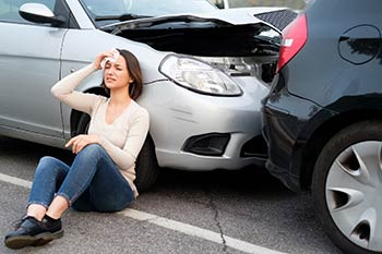Tampa Traumatic Brain Injury Attorney - Photo of a person sitting next to a car in an accident holding her head.