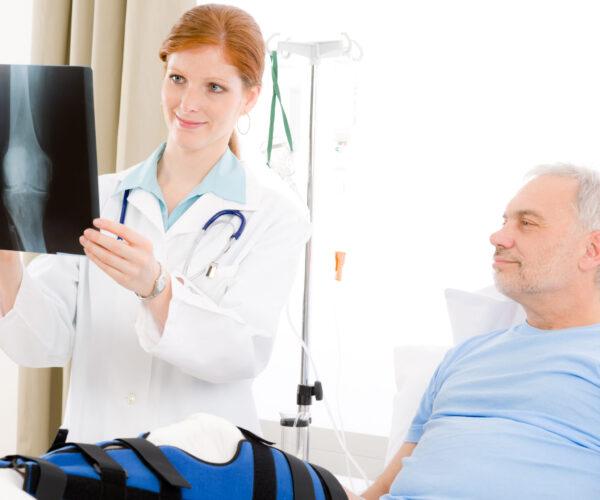 Hospital - female doctor examine x-ray senior patient broken leg